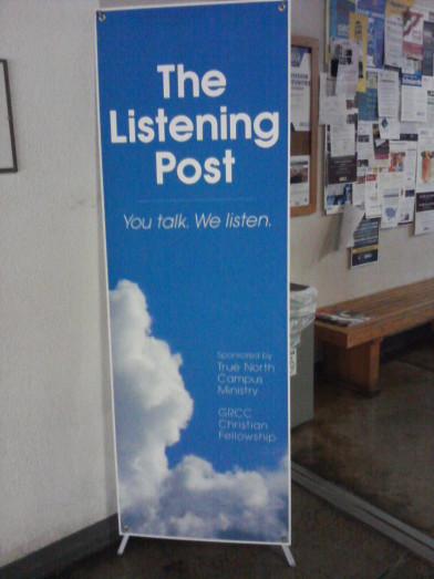 "Picture of a banner on a college campus. The vertical banner has blue skies and clouds in the background with a white border. The words on the banner reads ""The Listening Post. You Talk. We Listen."""
